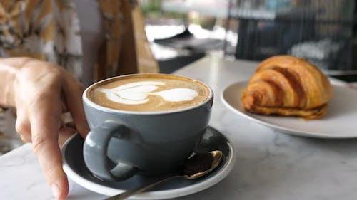 Female Hands Serving a Mug of Plant Based Latte