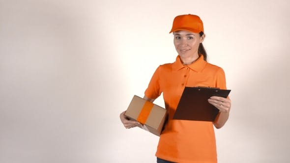 Thumbnail for Beautiful Female Courier in Orange Uniform Delivering a Parcel. Light Gray Backround,  Studio Shot