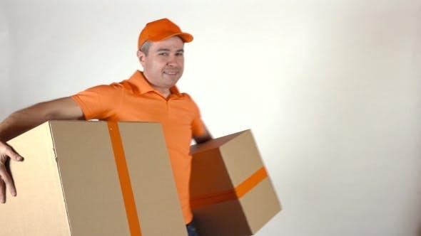 Thumbnail for Delivery Man In Orange Uniform Delivering Two Big Cartons. Light Gray Backround,  Studio Shot