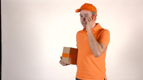 Thumbnail for Handsome Courier In Orange Uniform Talking On His Mobile Phone And Delivering a Parcel