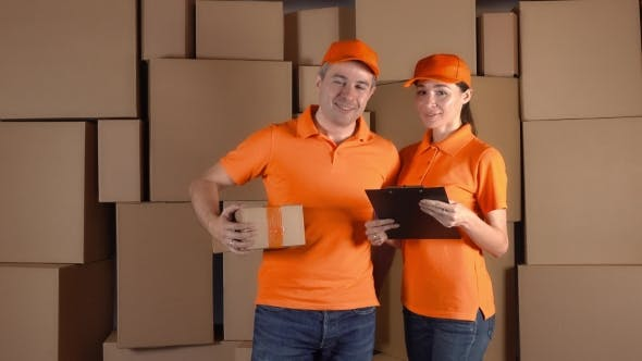 Thumbnail for Couriers In Orange Uniform Standing Against Brown Carton Stacks Backround. Delivery Company Staff