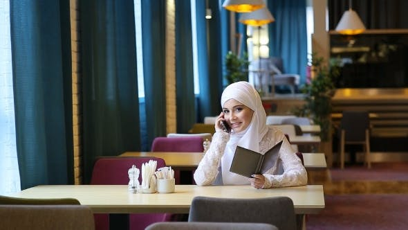 Thumbnail for Young Muslim Girl Uses Smartphone In Cafe