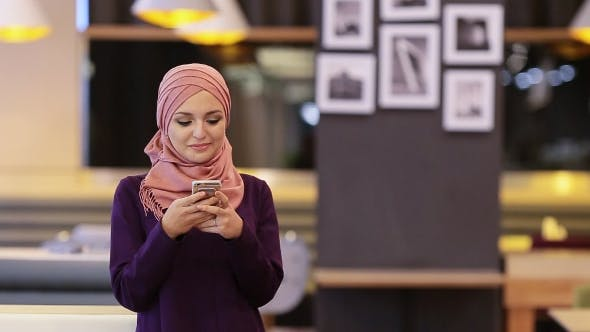 Thumbnail for Beautiful Muslim Girl Uses Smartphone In Cafe