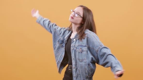 Thumbnail for Attractive Teenage Girl with Eyeglasses Dressed in Denim Jacket Dancing