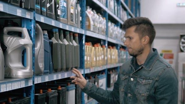 Thumbnail for Car Mechanic Man Choose Motor Oil For Car At Repair Service Station Supermarket