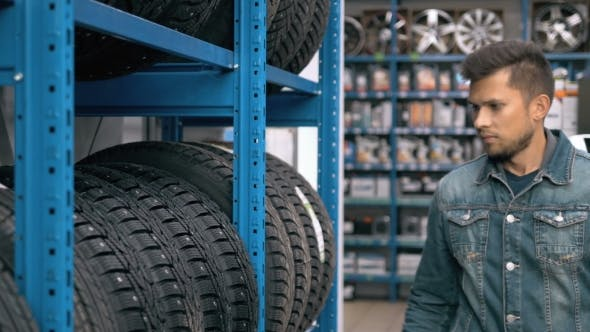 Thumbnail for Smiling Man Auto Mechanic Carrying New Tire In Tire Store Choosing For His Car