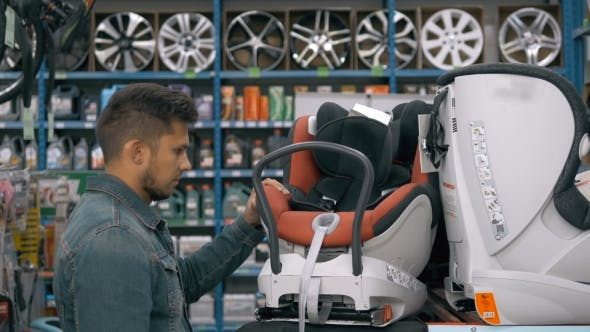 Thumbnail for Customer Choose Child Seat In Supermarket. Man In Car Shop Choosing Children Safety Babyseat