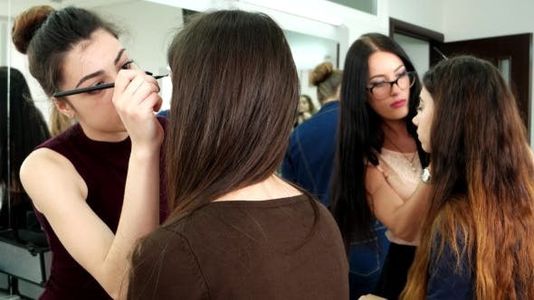 Cover Image for Girl Makeup Artists Do Make-up To Clients In The Salon, Evening Make-up To Fashion Shows