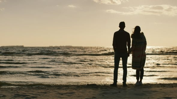 Cover Image for Silhouettes Of Young Couple Admiring The Sunset On The Sea, Embracing. Cool Day, The Wind Blows