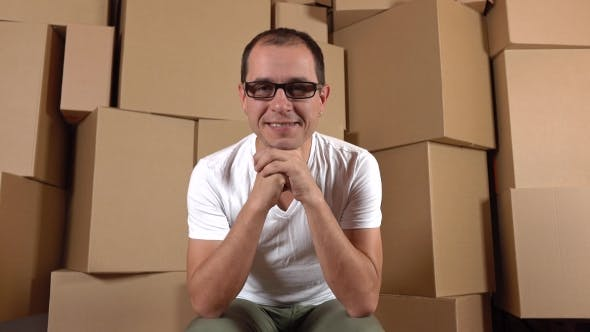 Thumbnail for Confident Smiling Owner Of Internet Shop Sitting Against Multiple Carton Stacks.  Clip