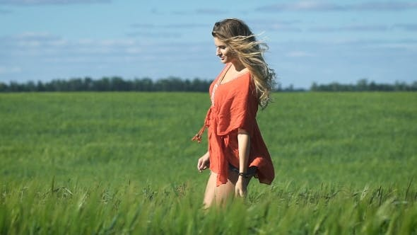 Thumbnail for Beautiful Blonde Young Happy Woman In a Red Shirt Walking Slowly