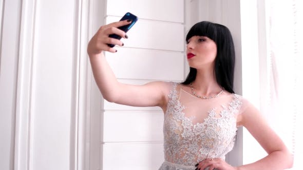 Thumbnail for Selfie Photo At The Window, Beautiful Girl Smiling Mobile Phone With Touch Screen Makes The Picture