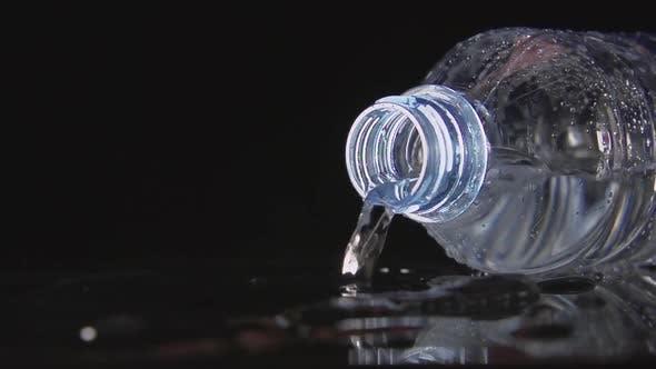 Thumbnail for Plastikflasche fällt auf einen schwarzen Tisch und Wasser gießt daraus