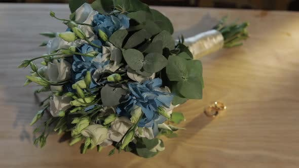 Thumbnail for Wedding Rings Lie Near Beautiful Wedding Bouquet on the Wooden Table