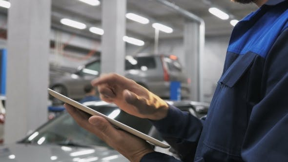 Thumbnail for Smiling Mechanic Using a Tablet Pc At The Repair Garage Service