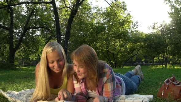 Thumbnail for Happy Teenage Girls Reading a Book Outdoors.