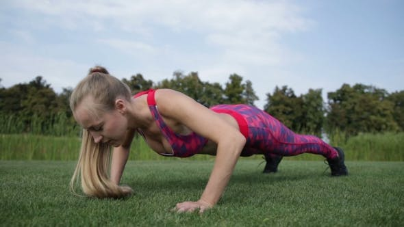 Gorgeous Blonde Woman Doing Some Push Ups In Park