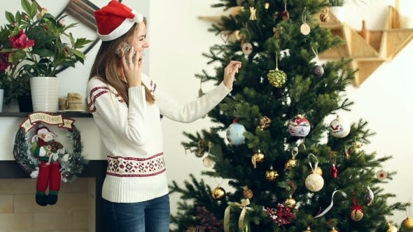Thumbnail for Pretty Girl Talking On The Phone Nearby Christmas Tree