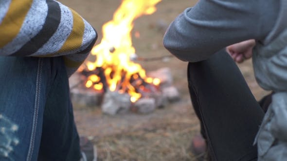 Group Of People Having a Party Outdoors And Cooking Meat On Campfire