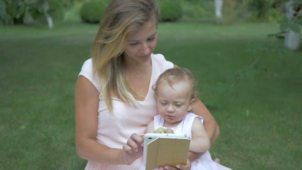 Thumbnail for Mutter und Tochter Blick auf eine Tablette.