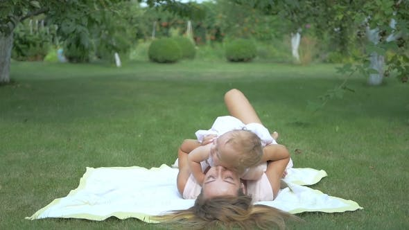 Thumbnail for Baby With Her Mom Lying on the Rug in the Garden.