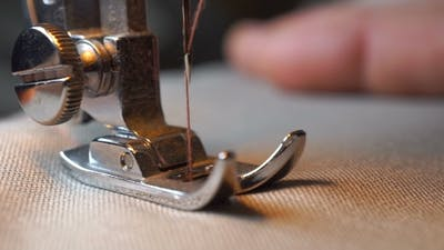 Woman Sews On The Sewing Machine.