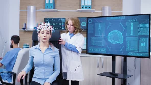 Neurology Female Doctor Making Adjustments To Brainwaves Headset