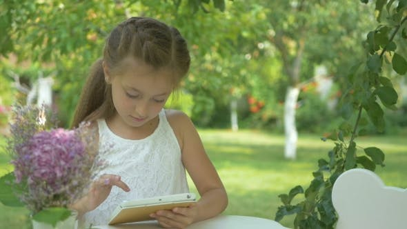Thumbnail for The Girl Playing on the Tablet in the Garden