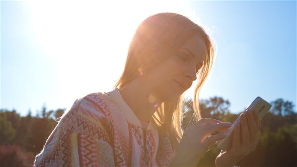Thumbnail for Happy Smiling Girl Using a SmartPhone in City Park Sitting on Grass 5
