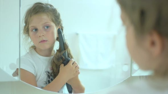Thumbnail for The Girl Twisting a Hair on the Curling Iron Near the Mirror