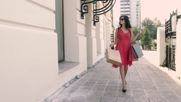 Thumbnail for Happy Young Woman Is Walking Down The Street After Shopping