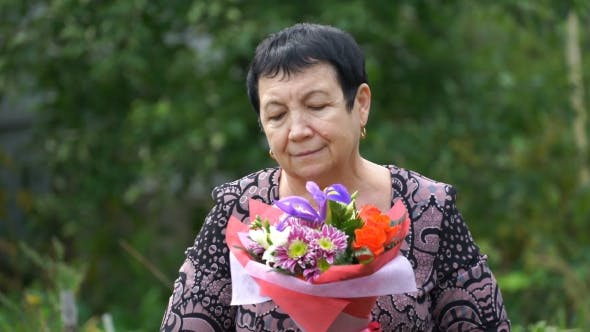 Thumbnail for Footage Elderly Woman Holding a Bouquet Of Flowers Outdoors.