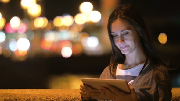 Thumbnail for Girl In The City At Night. She Uses Her Tablet, Big Blurred City Lights On The Background. Wind