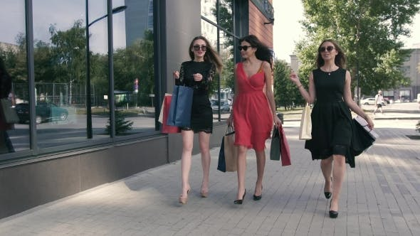 Thumbnail for Three Attractive Young Ladies Are Walking With Their Purchases