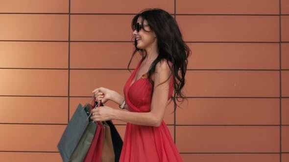 Thumbnail for Beautiful Girl In Red Dress Turns Around With Her Shopping Bags
