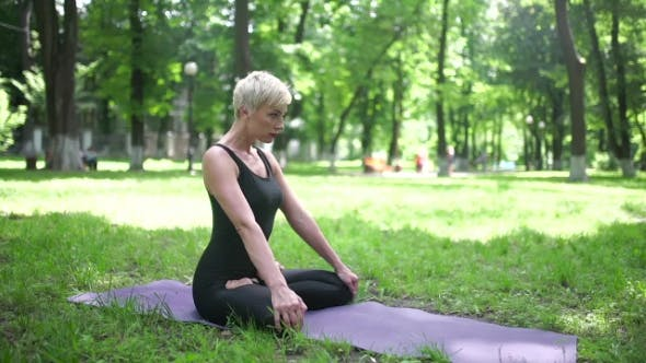 Thumbnail for Woman Sitting In Lotus Pose In The Park.