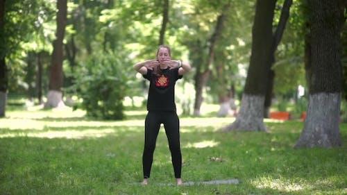 La fille est engagée dans la gymnastique dans le parc.