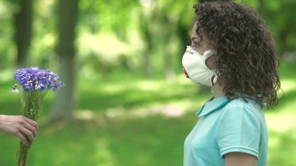 Thumbnail for Girl In Respirator Give Flowers.