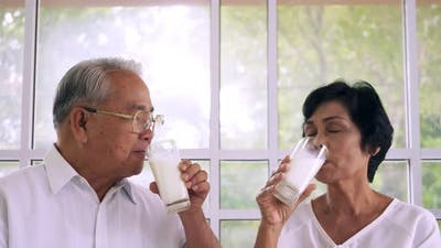 An elderly couple are drinking milk every morning of the day.