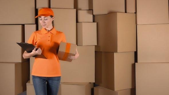 Thumbnail for Pretty Female Courier in Orange Uniform Delivering a Parcel