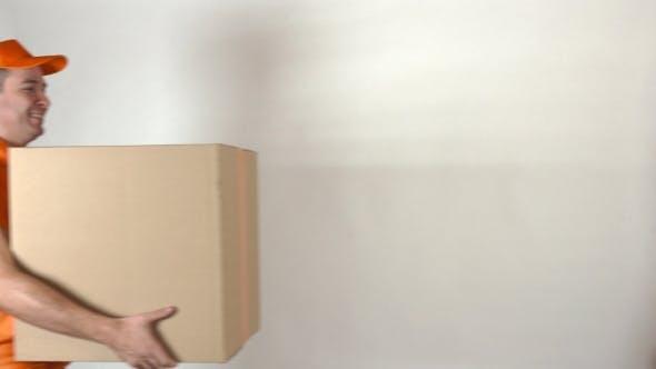Thumbnail for Male Courier In Orange Uniform Delivering Big Parcel