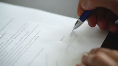 Businessman Sitting at Office Desk Signing a Contract With Shallow Focus on Signature