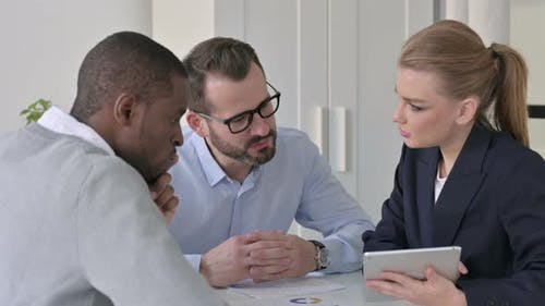 Professional Male and Female Business People Talking in Office