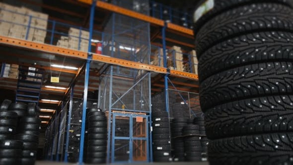 Thumbnail for Car Tires At Warehouse In Tire Store. A Huge Warehouse Of a Car Tires With Elevator