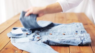 Woman Folding Denim Jacket On Wooden Table At Home
