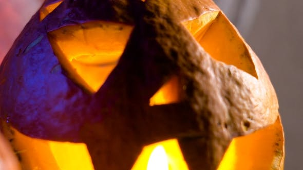 Thumbnail for Pumpkin Head Lit From Within, Her Eyes, Nose And Mouth Flickering Candle Light. All Saints Day