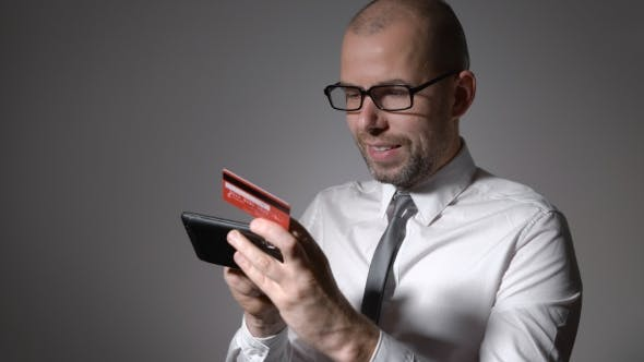 Thumbnail for A Man With a Beard Businessman Holding a Mobile Phone And The Hands Of The Credit Card.