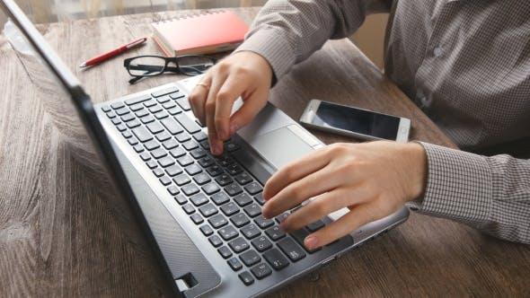 Man-Arms Tippen auf Tastatur am natürlichen Hartholz-Schreibtisch