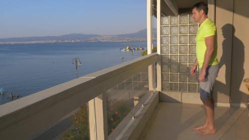Mann Anfang Push-ups auf dem Balkon mit Meerblick Hintergrund