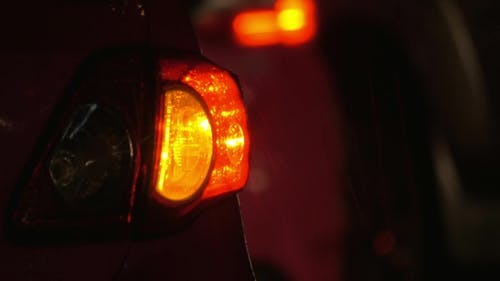 Car With Hazard Lamps At Rainy Night